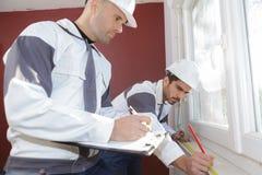 使用测量的磁带的建筑工人在新房 免版税库存照片
