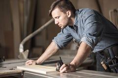 使用测量的磁带的年轻木匠 免版税库存照片