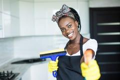 使用浪花的画象年轻非洲妇女抹玻璃窗 免版税库存图片