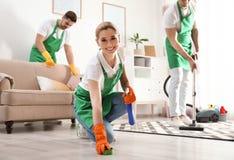 使用海绵和洗涤剂的妇女为清洗与她的队的地板 库存照片