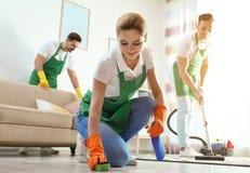 使用海绵和洗涤剂的妇女为清洗与她的队的地板 免版税库存图片