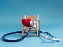 使用深蓝色听诊器的红色心脏在蓝色背景 爱的概念和由心脏的有同情心的患者或病态在trave 免版税库存图片