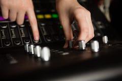 使用混音器的女性音频工程师的手 免版税图库摄影