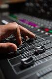 使用混音器的男性音频工程师的手 免版税库存照片