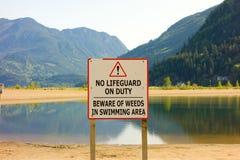 使用湖的标志警告游泳者责任自负 免版税库存图片