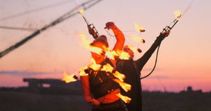 使用火焰喷射器和转动,一个小组有火的专业马戏团演员在慢动作显示舞蹈展示 影视素材