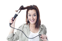 使用烫发钳的年轻微笑的女孩 免版税库存照片