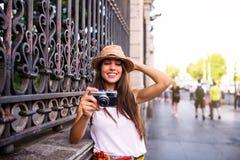 使用照片照相机的年轻美丽的旅游妇女 免版税库存图片