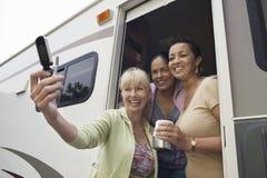 使用照相机电话的三名妇女在住房汽车 免版税库存照片