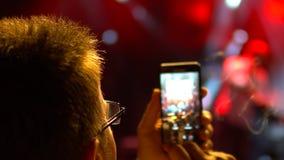 使用照相机电话的观众在音乐会 免版税库存图片