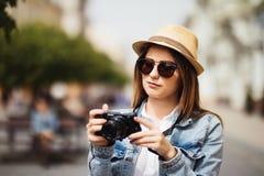 使用照相机的可爱的摄影师妇女游人户外在新的城市 库存图片