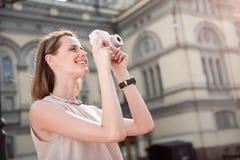 使用照相机的逗人喜爱的少妇 免版税库存照片