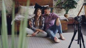 使用照相机,逗人喜爱的年轻夫妇记录他们的互联网vlog的录影,他们与追随者和拥抱谈话 股票视频