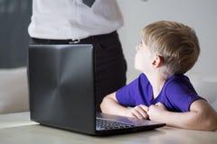 使用父亲的膝上型计算机的孩子 库存照片