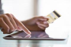 使用片剂个人计算机和信用卡的妇女 免版税库存图片