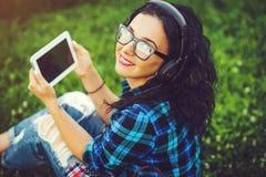 使用片剂个人计算机和耳机的愉快的俏丽的女孩听mu 免版税图库摄影