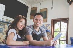 使用片剂个人计算机的两个咖啡馆工作者 图库摄影