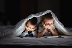使用片剂个人计算机的两个孩子在毯子下在晚上 免版税库存图片