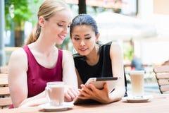 使用片剂个人计算机的两个年轻女性最好的朋友户外在tr 免版税库存照片