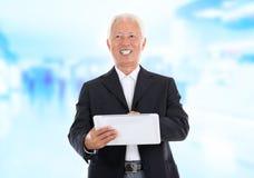 使用片剂个人计算机的亚洲高级生意人 免版税库存照片
