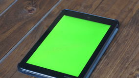 使用片剂个人计算机的人` s有在木表上的绿色屏幕的与各种各样的手势 股票录像