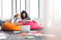 使用片剂个人计算机的创造性的女实业家,当放松在装豆子小布袋椅子在办公室时 免版税库存图片