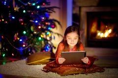 使用片剂个人计算机的可爱的小女孩由一个壁炉在圣诞节晚上 免版税库存图片