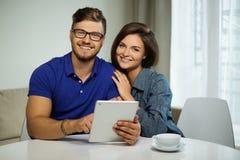 使用片剂个人计算机的夫妇在家 免版税库存照片