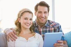 使用片剂个人计算机的夫妇在长沙发,当看照相机时 免版税库存照片