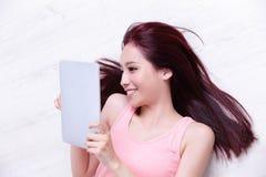 使用片剂个人计算机的妇女微笑 免版税图库摄影