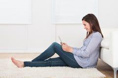使用片剂个人计算机的妇女,当坐地毯时 图库摄影