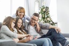 使用片剂个人计算机的家庭在有圣诞树的沙发在背景中 免版税图库摄影