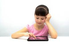 使用片剂个人计算机的小女孩 库存图片