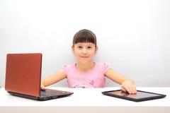 使用片剂个人计算机的小女孩 免版税库存照片