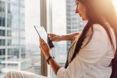 使用片剂个人计算机的少妇坐扶手椅子在窗口附近有城市视图 免版税库存照片