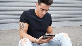 使用片剂个人计算机的年轻人室外在城市 免版税库存照片