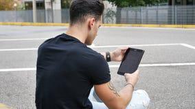 使用片剂个人计算机的年轻人室外在城市 免版税库存图片