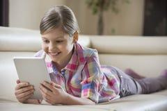 使用片剂个人计算机的微笑的女孩,当在家时说谎在沙发 库存图片