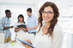 使用片剂个人计算机的微笑的女实业家 免版税库存图片