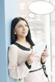 使用片剂个人计算机的微笑的年轻女商人,当站立轻松的近的窗口在她的办公室时 免版税库存照片