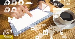 使用片剂个人计算机的手有图表和地图覆盖物的  库存图片