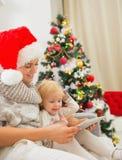 使用片剂个人计算机的母亲和孩子在圣诞树附近 图库摄影