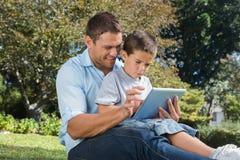 使用片剂个人计算机的爸爸和儿子在公园 库存照片