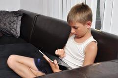 使用片剂个人计算机的男孩 免版税库存照片