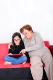 使用片剂个人计算机的祖母和孙女 库存图片