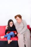 使用片剂个人计算机的祖母和孙女 免版税库存图片
