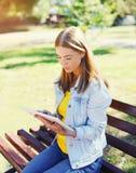 使用片剂个人计算机的美丽的少妇坐长凳在城市 免版税库存图片