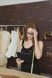 使用片剂个人计算机的美丽的年轻女性时装设计师 免版税库存图片