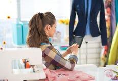 使用片剂个人计算机的裁缝妇女在工作 查出的背面图白色 库存照片