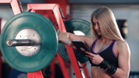 使用片剂个人计算机的运动的妇女在健身房 库存图片